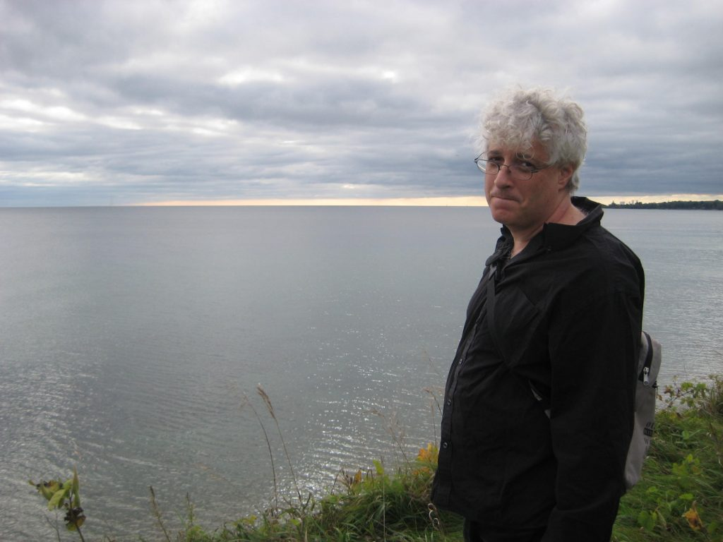 Person with glasses and white hair standing by a large body of water.