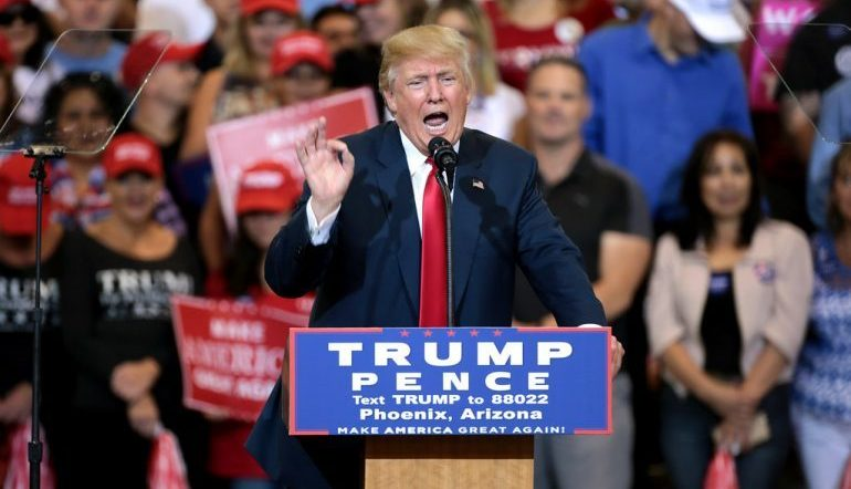 """Donald Trump speaking behind a podium reading """"Trump Pence"""" in front of a crowd"""