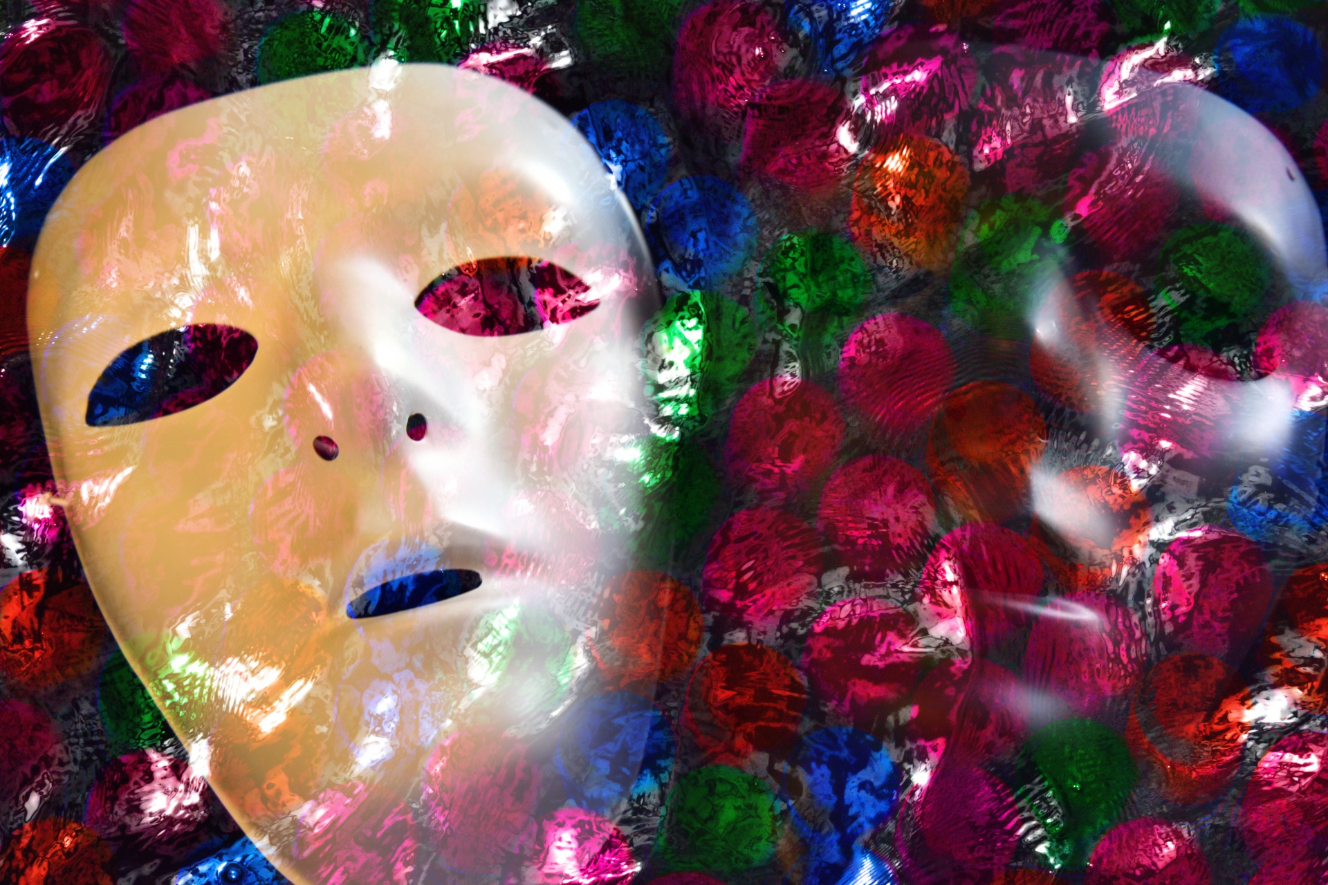 On the left, a blank drama mask over a colorful, polka dot background with the illusion of another faded mask on the right.