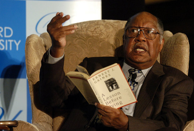 """Man with glasses sitting in an armchair reading from """"A Lesson Before Dying"""" by Ernest J. Gaines."""