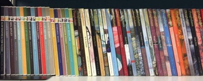 Several Ploughshares issues lined up on a bookshelf with the spines facing out.