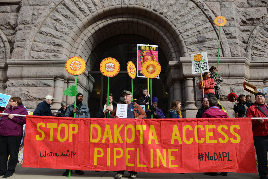 """Protesters behind a red banner that reads """"Stop Dakota Access Pipeline."""""""