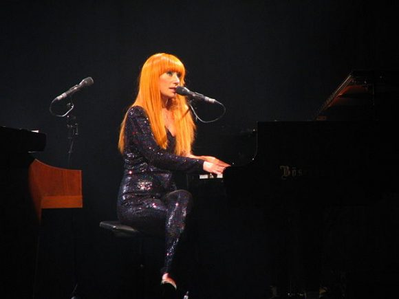 Woman with long orange hair sitting at a piano and singing into a microphone.