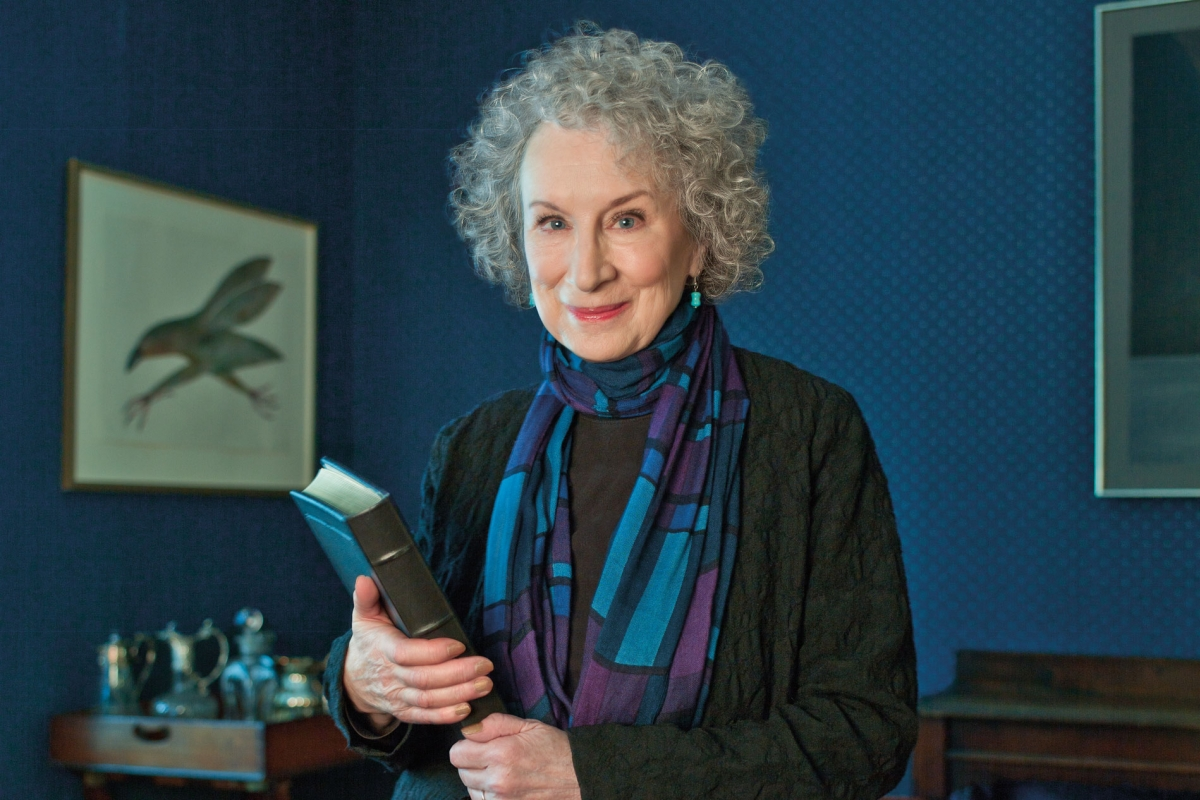 Woman with curly gray hair holding a book and posing for the camera in front of a blue wall.