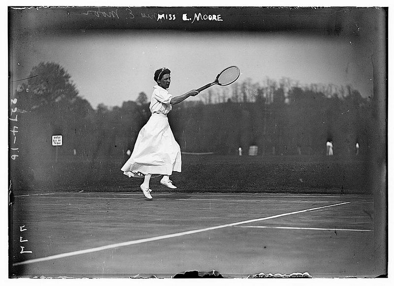 Old photograph of a woman wearing a white dress and holding a racquet.