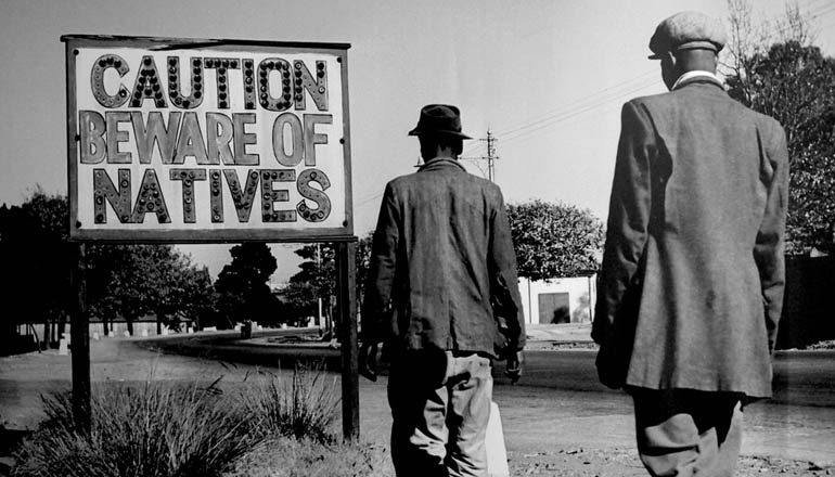 """Two men in suits walking towards a sign that reads """"Caution Beware of Natives."""""""