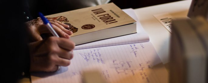 person writing on notebook near book