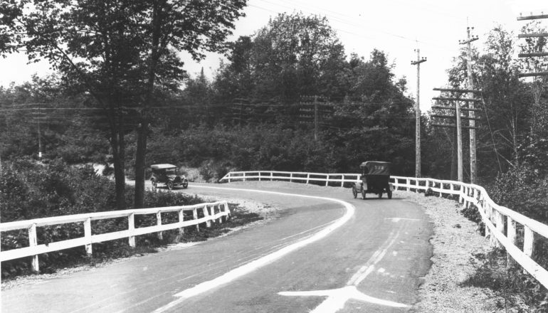 black and white photo of old cars driving on road