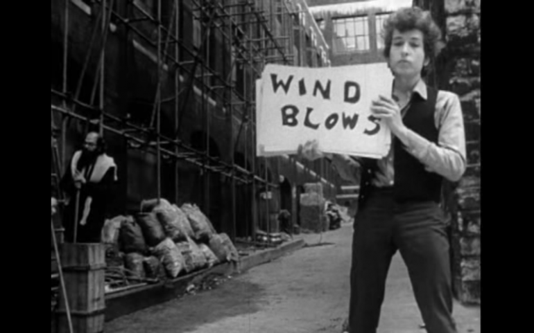 "Clip of Bob Dylan's ""Subterranean Homesick Blues"" video of Bob Dylan holding up a handwritten sign reading ""Wind Blows"" in an alley"