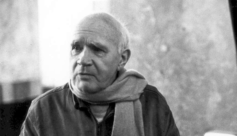 Old man wearing a scarf and leather jacket looking away from the camera.
