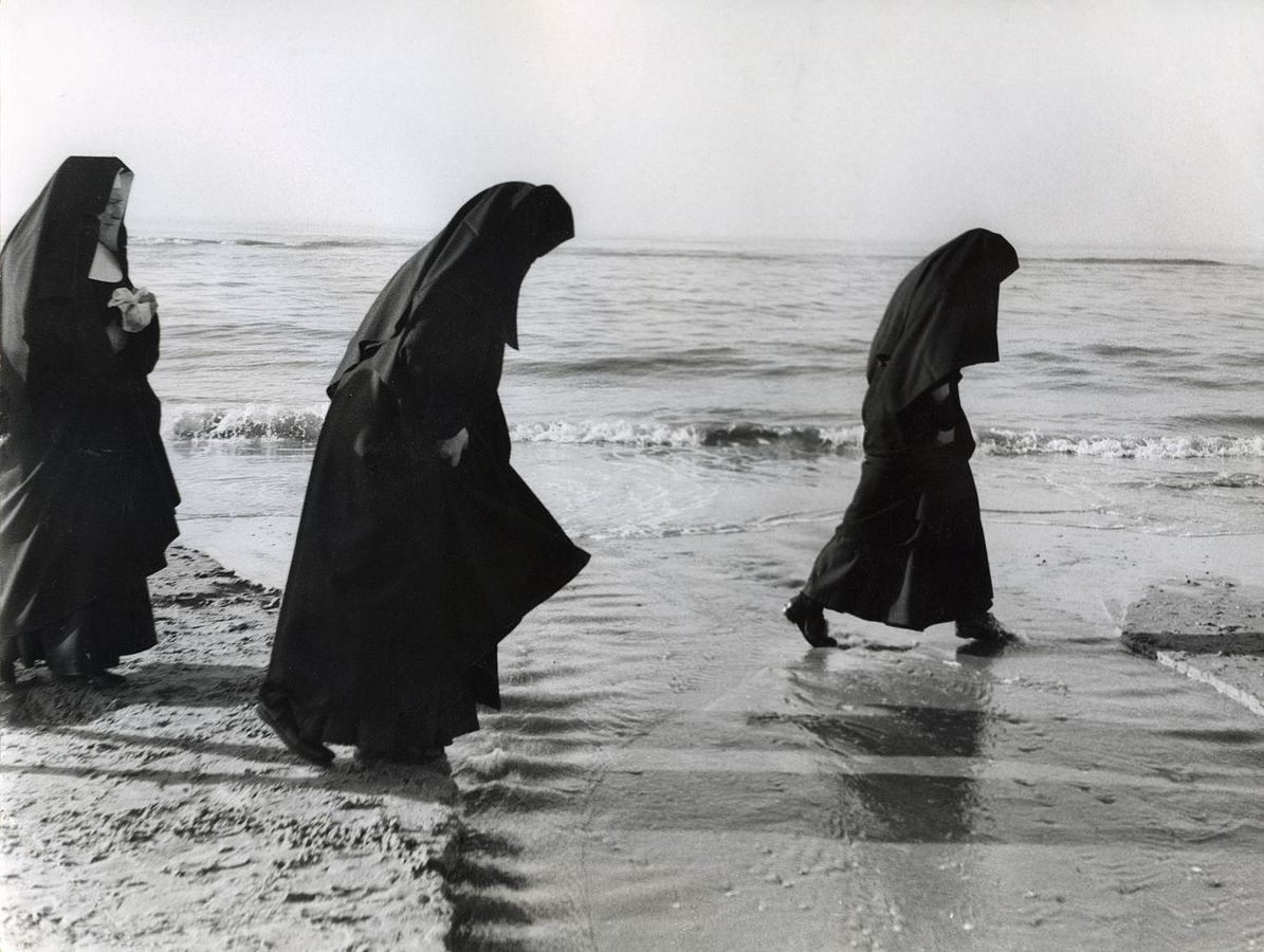Nuns dressed in black robes walking on a beach.