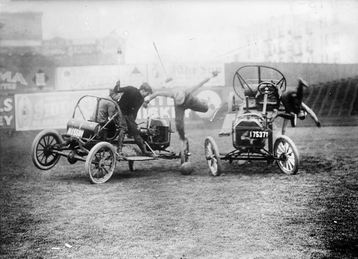 Old photograph of people playing on old car-looking prototypes.