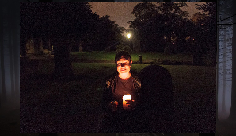 Person holding a candle and sitting outside at night.