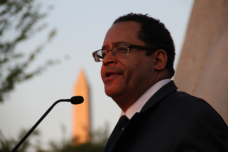 Man with glasses speaking into a microphone.