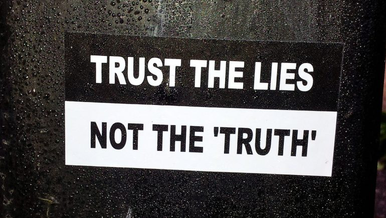 """Text that reads """"Trust the Lies Not the 'Truth'"""" on a black and white background."""