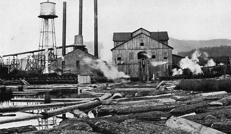 Old photo of a factory with smoke surrounding it, and logs laying on the ground.