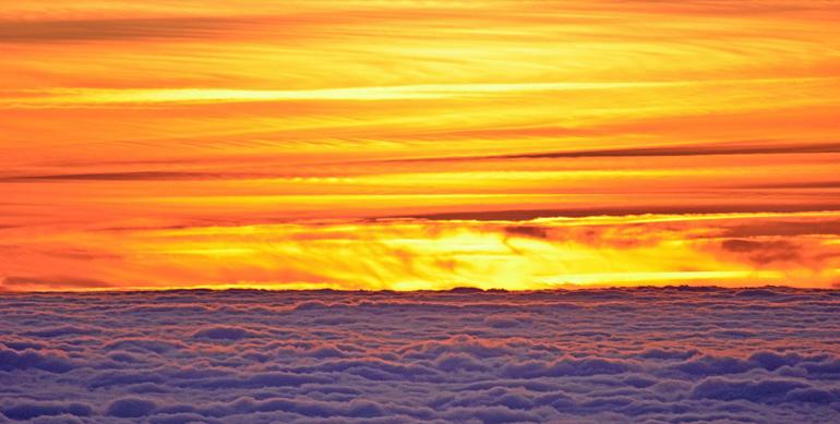 Orange sunset above fluffy clouds.