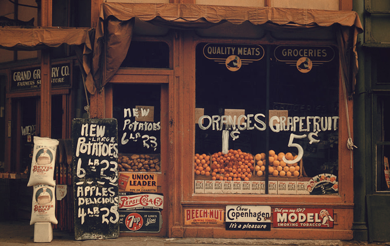 Produce corner store advertising oranges and grapefruit in the window.