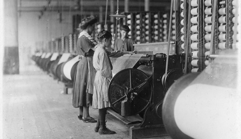 Woman and young girl standing at a machine.