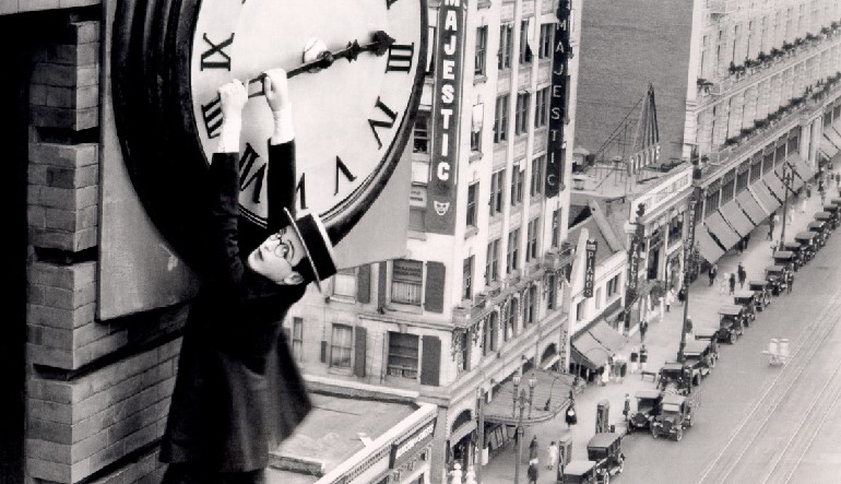 Man hanging from the hands of a large clock.