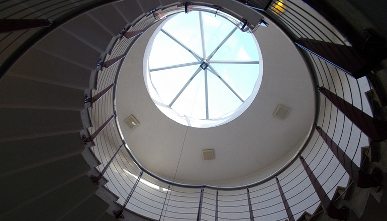 A spiral staircase leading to a skylight.