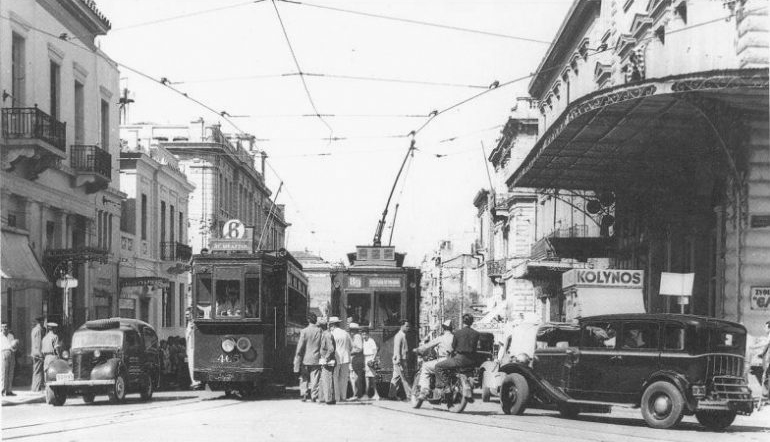 Old photo of people boarding a trolley.