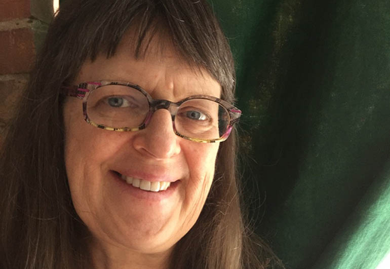 Photo of a woman with bangs wearing glasses and smiling at the camera.