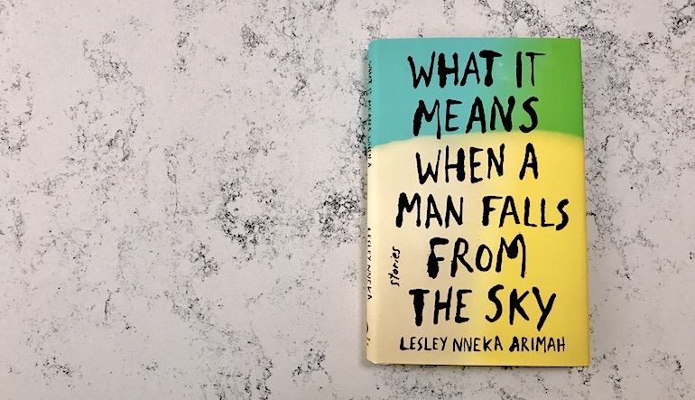 """Book cover for """"What it Means When a Man Falls From the Sky"""" by Lesley Nneka Arimah. The top of the book is blue and green, and the bottom is yellow."""