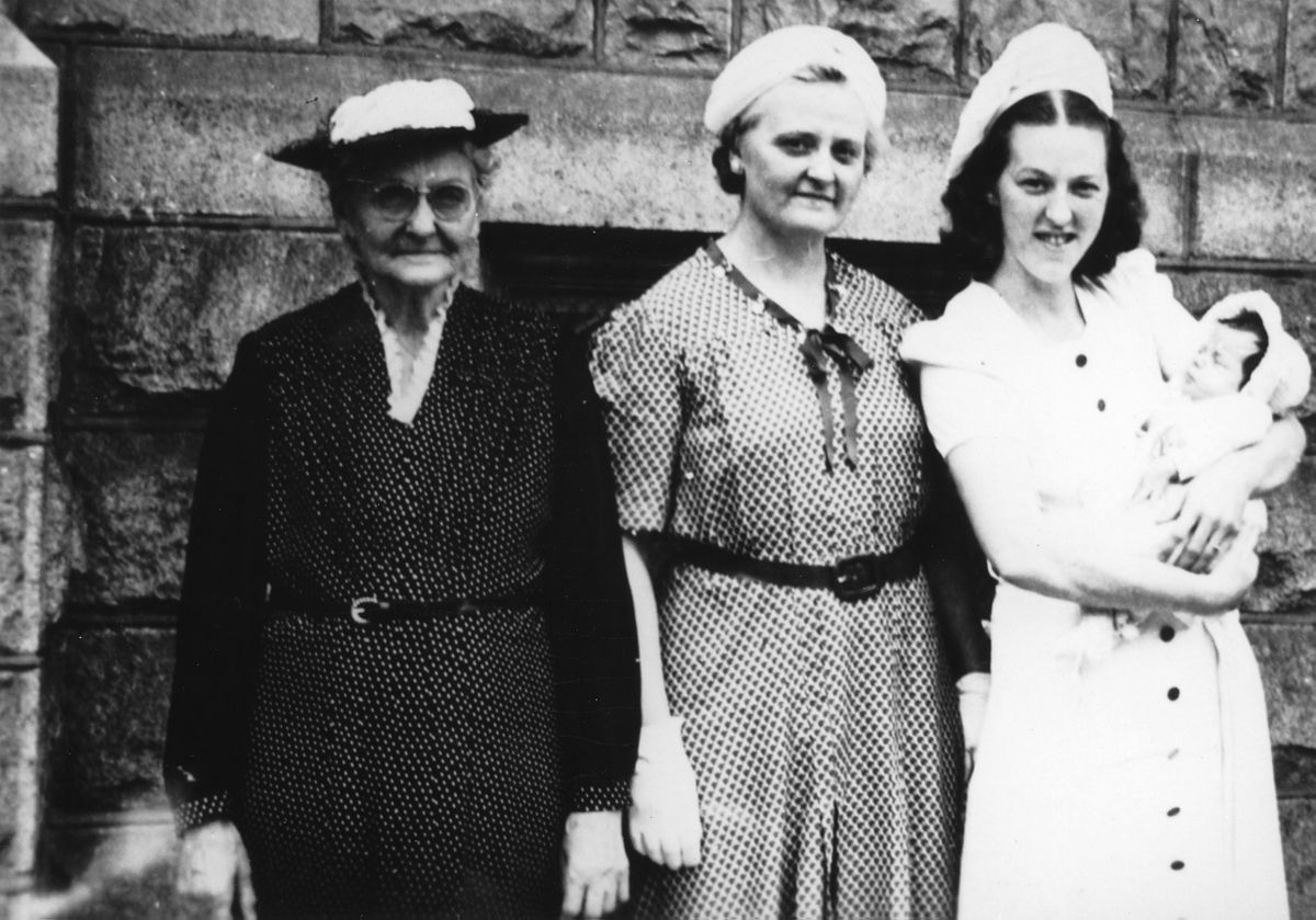 Three women standing next to each other with the one on the right holding a baby.