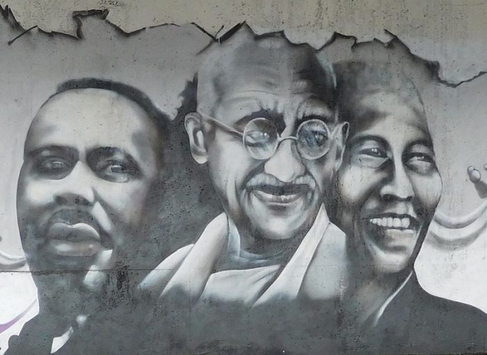 Faces of three men painted on a wall.