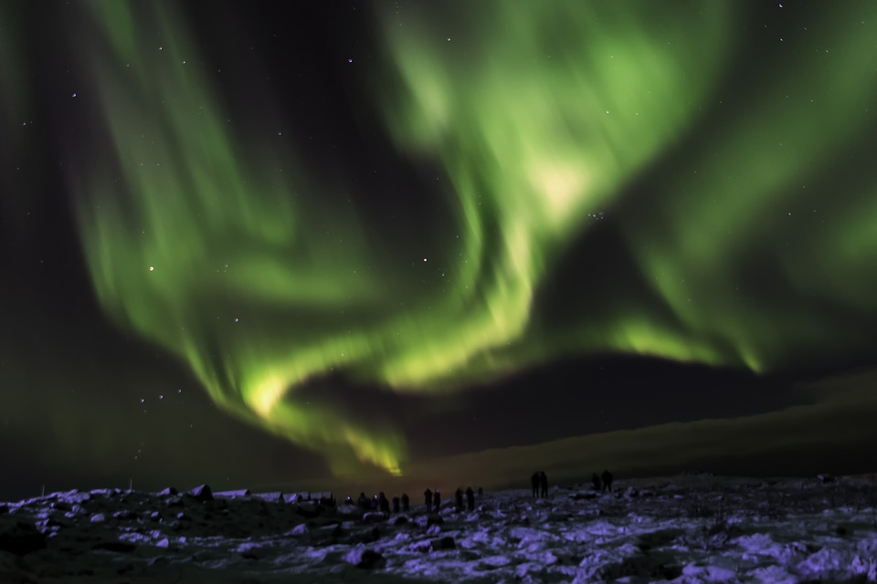 Green Northern Lights over a snowy landscape.