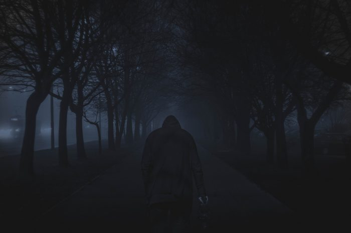 Hooded figure standing in front of a dark walkway lined by trees.