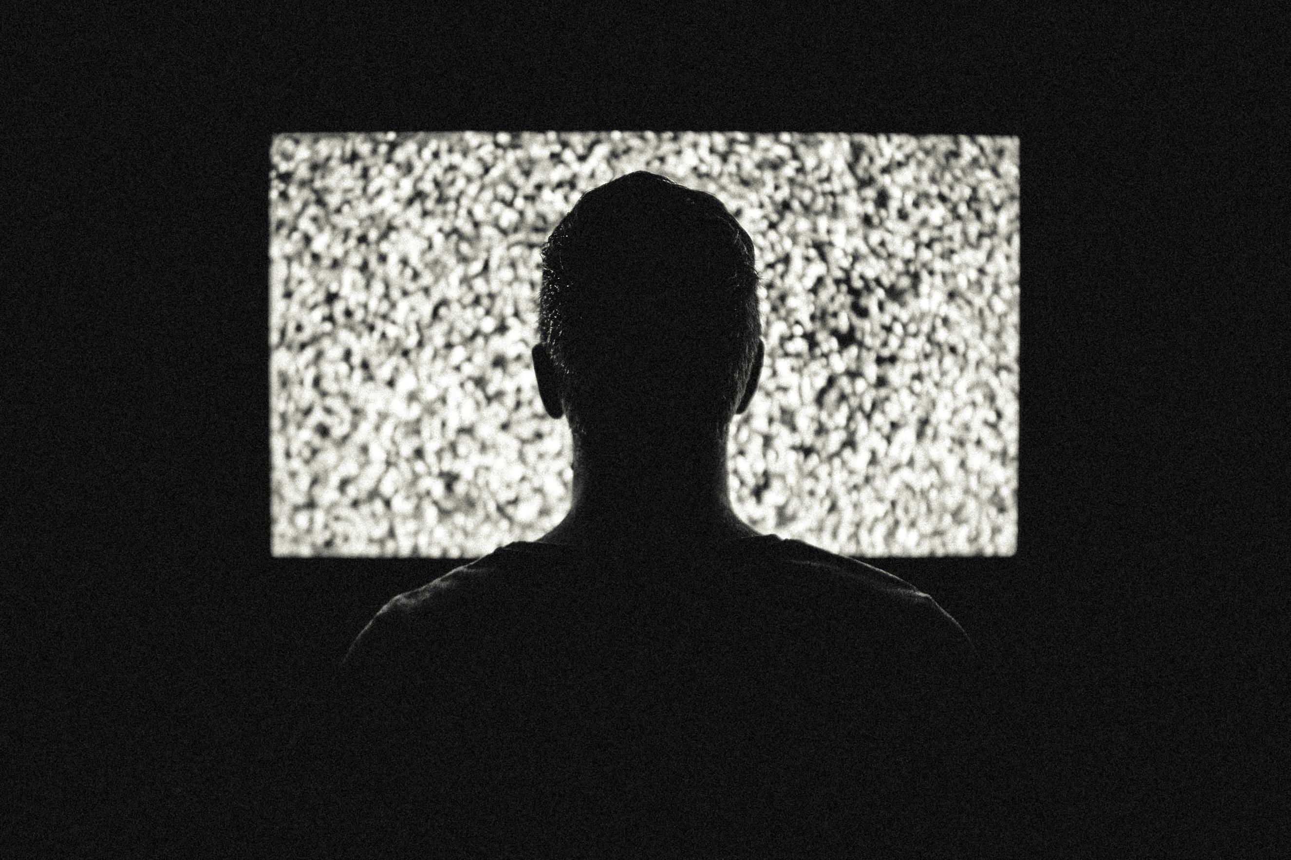 Man staring at TV static.