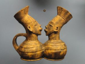 2 small statues/vases with faces, facing each other