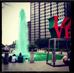"""city fountain with red sculpture nearby saying """"LOVE"""""""