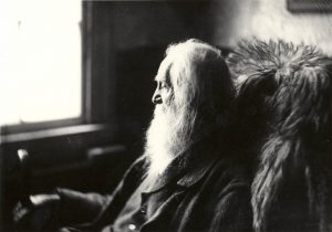 Old man with long beard sitting on a chair.