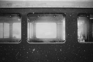 Exterior train windows with snow falling.
