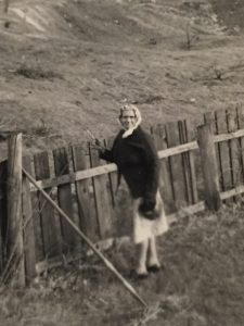 old photo of woman standing in front of fence and field