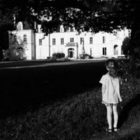 in black and white, a young girl, back to camera, looks at a white mansion-like building some distance away