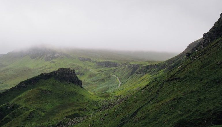 green mountainside with a misty background