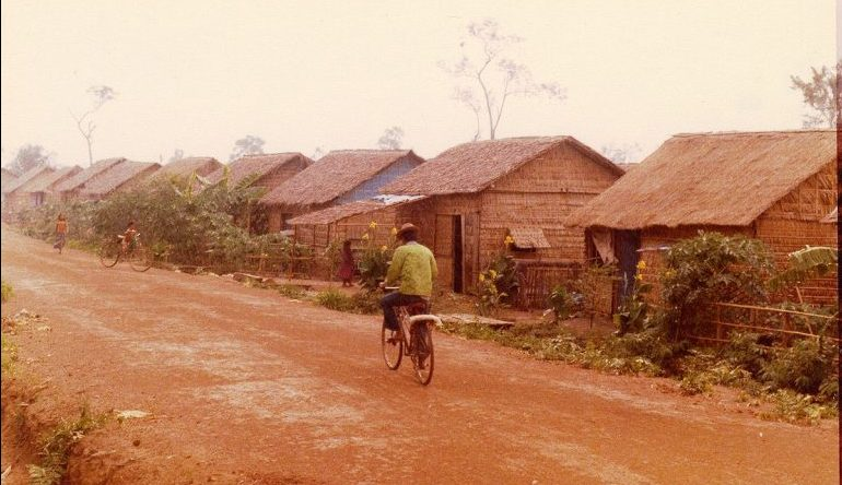 person rides bike on dirt road lined with houses