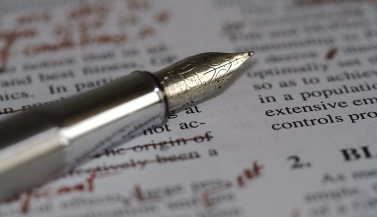 fountain pen in foreground, text with corrections made in red ink in background