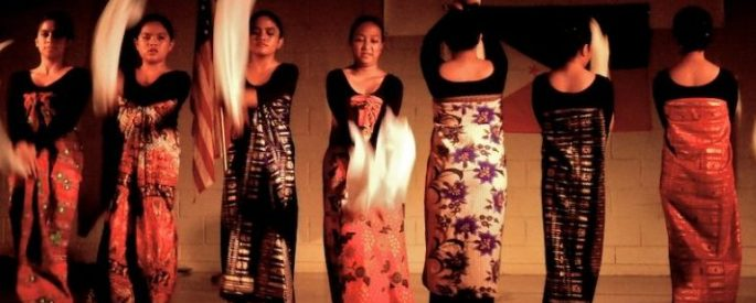 women in patterned cloth dresses, in motion, perhaps in dance