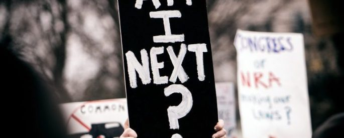 "Hands holding a black sign that says ""Am I next?"" in white lettering"