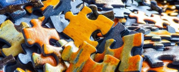 unmatched jigsaw puzzle pieces, in orange, blue, and green