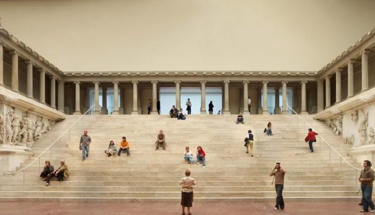 people sitting on wide steps inside a museum