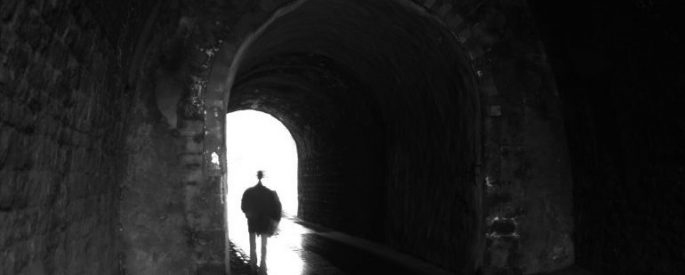 shadowing person walks under a tunnel