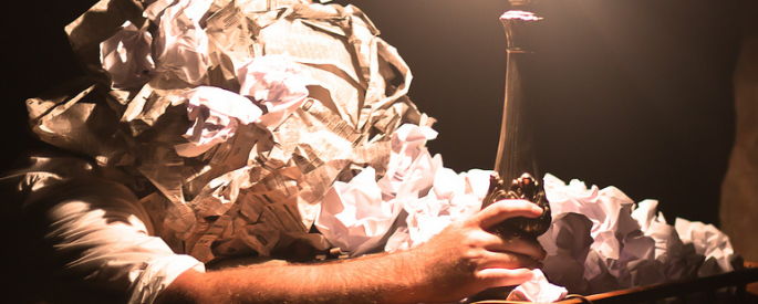 man buried under a pile of crumpled paper holds a lamp