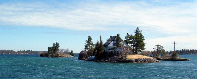 house on a little island in blue waters