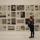 woman looking at a wall of what appear to be newspaper pages